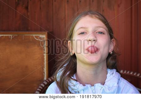 Young naughty girl sticking out tongue sitting against wooden wall. Head and shoulders portrait