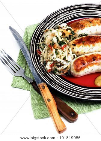 Delicious Grilled White Munich Sausages with Pickled Cabbage and Mustard Sauce on Red Striped Plate isolated on White background