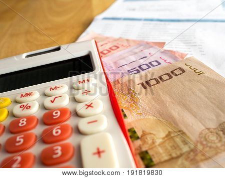 The red calculator is placed on a banknote.After calculating the bill of payment.