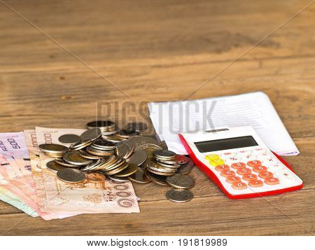 The red calculator banknote and coin is placed on a wooden table .After calculating the bill of payment.