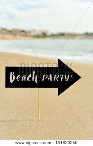 closeup of a black signboard in the shape of an arrow sign with the text beach party written in it on the sand of a beach