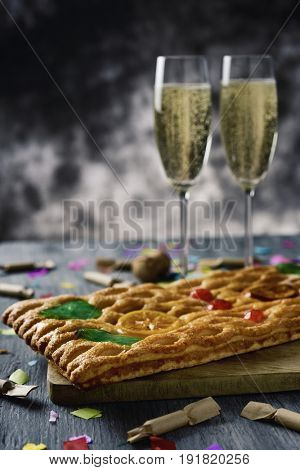 closeup of a coca de Sant Joan, a typical sweet flat cake from Catalonia, Spain, eaten on Saint Johns Eve, on a rustic table, a pair of glasses with champagne, firecrackers and confetti poster