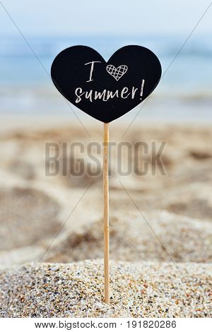 closeup of a black heart-shaped signboard with the text I love summer written in it, on the sand of a lonely beach