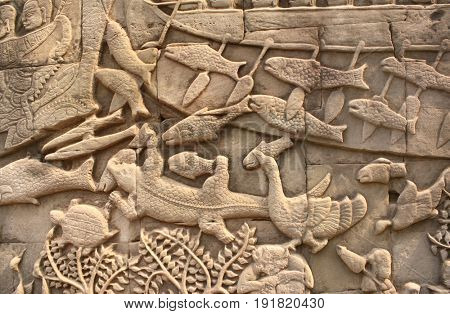 Wall carving with animals - fish, crocodile, bird, Prasat Bayon Temple, in famous landmark Angkor Wat complex, khmer culture, Siem Reap, Cambodia