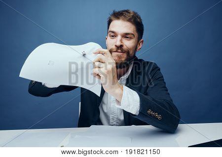 Businessman punctured documents, documents, businessman on blue background, businessman working.