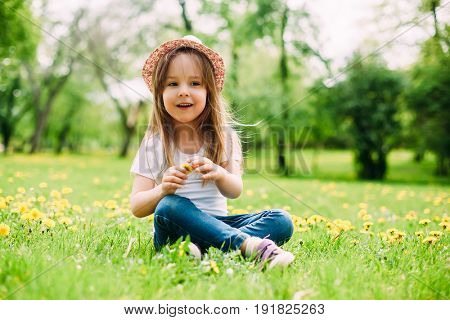 Cute little girl with hat siting on the grass