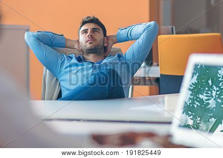 caucasian business person sitting in office thinking daydreaming hands behind head