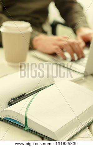 Open notepad with black pen on work-table. Paper cup of coffee, office stuff, laptop and working man on background, vertical, toned