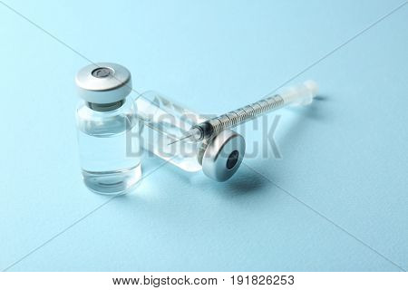 Vaccine in vials with syringe on color background