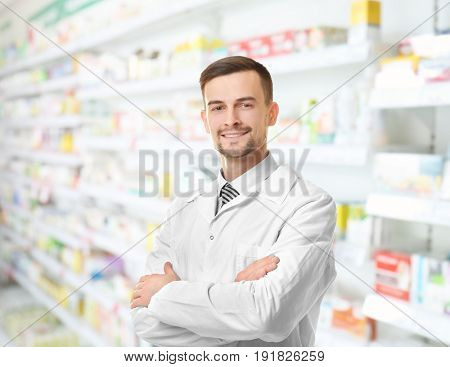 Young male pharmacist at work. Blurred shelves with pharmaceutical products on background