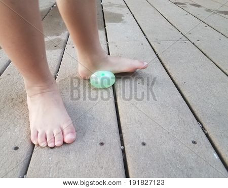 child's foot on water balloon trying to pop it on deck