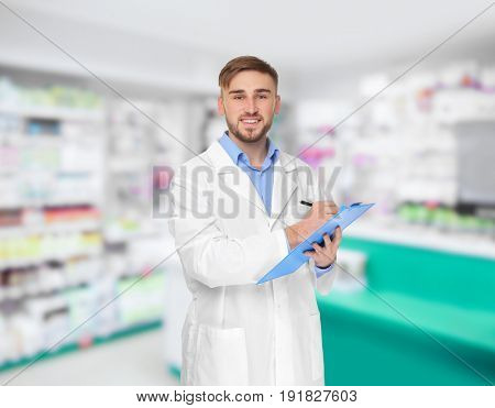 Young male pharmacist with clipboard at work. Blurred shelves with pharmaceutical products on background