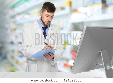 Male pharmacist with clipboard at work. Blurred shelves with pharmaceutical products on background