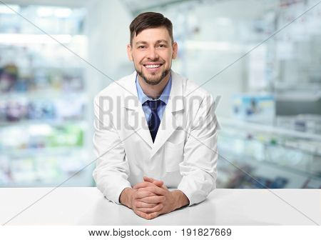 Male pharmacist near counter at work. Blurred shelves with pharmaceutical products on background