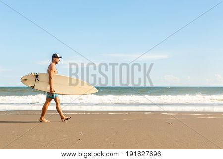 Handsome Man With Surfing Board On Spot.