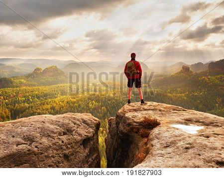 Tall Man Enjoy Freedom On Peak Of Mountain Edge. Alone Tourist  Watching Over Misty Valley