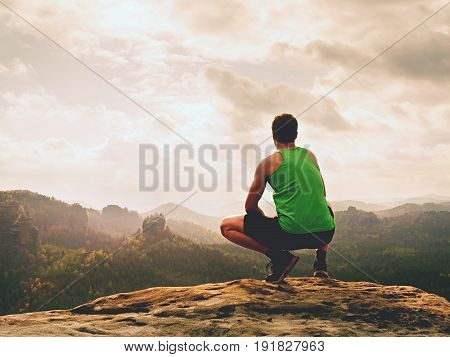 Adult Hiker In Black Shorts And Green Singlet Sit On Mountain  Edge. Man Enjoying View