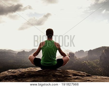 Alone Man Is Doing Yoga Pose On The Rocks Peak Within Misty Morning. Middle-aged Man Practicing Yoga