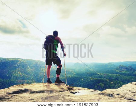Man With A Crutches In Nature. Tourist With Broken Leg On Crutches. Traveler With Hurt Leg In Bandag