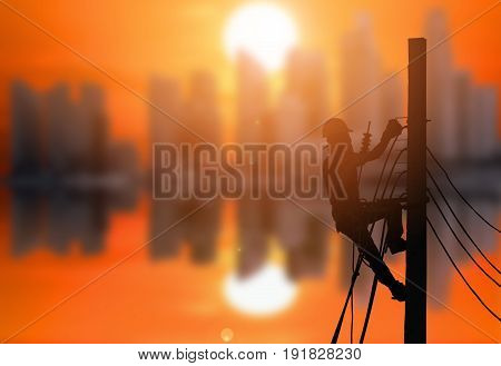 Silhouette of an electrician are climbing on electric poles to install power lines with the beautiful sunset at the city background.