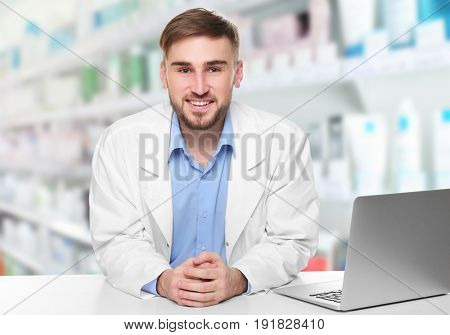 Young male pharmacist near counter with laptop at work. Blurred shelves with pharmaceutical products on background