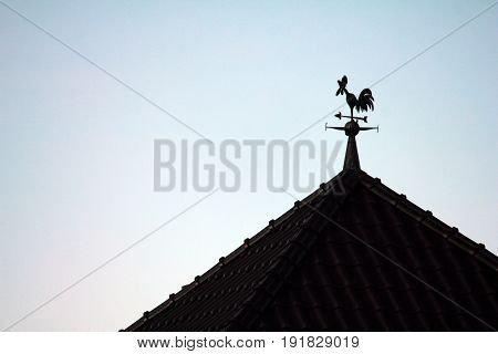 silhouette of a rooster weather vane on the roof