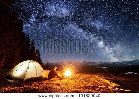 Male Tourist Have A Rest In His Camp Near The Forest At Night. Man Sitting Near Campfire And Tent Un