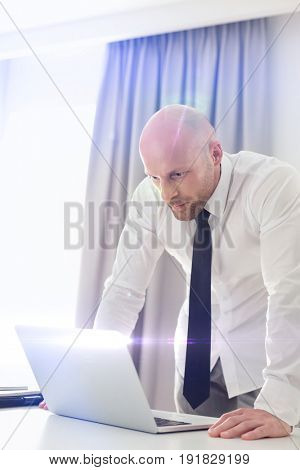 Mid adult businessman using laptop at table in home office
