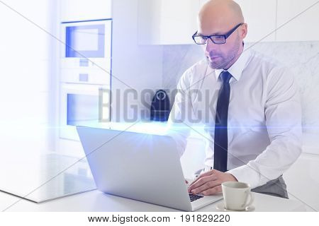 Mid adult businessman using laptop at kitchen counter