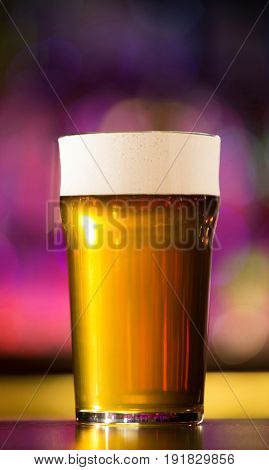 Close up of a beer glass standing on the bar counter