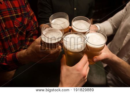 Close-up of five men toasting with beer while sitting in beer pub together