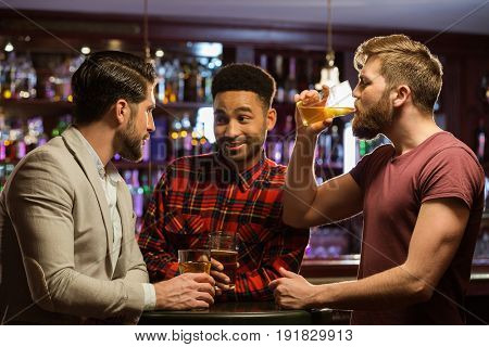 Happy laughing male friends catching up over pints in a bar