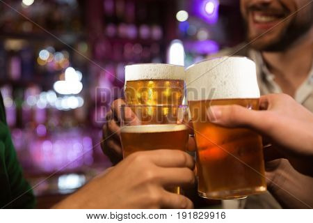 Close-up of three happy young men toasting with beer while sitting in beer pub together