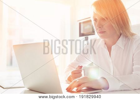 Beautiful mid adult businesswoman using laptop while having coffee at home