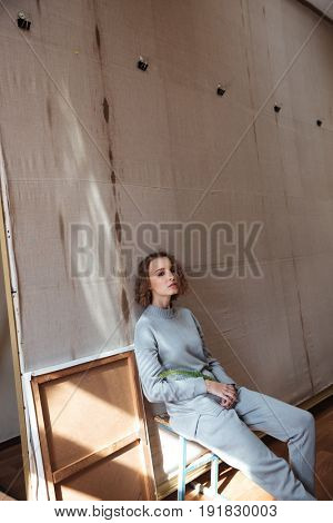 Young woman sitting and leaning against a canvas backdrop