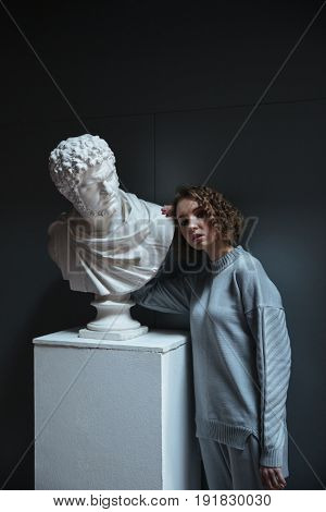 Young woman with curly hair wearing sportsuit standing near bust in museum