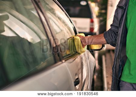Male worker is cleaning a car with sponge at service station