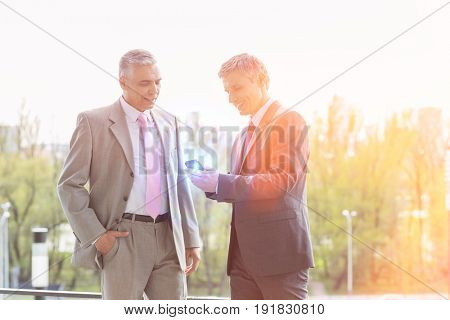 Businessmen using cell phone together outdoors