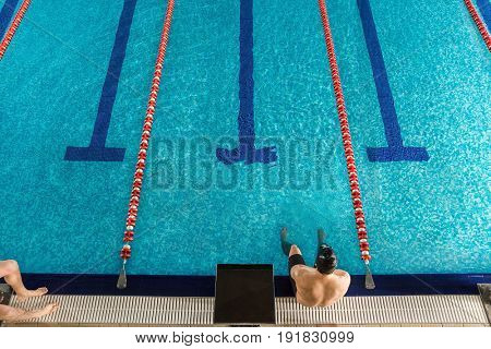 Top view of a male swimmer sitting on the edge of a swimming pool
