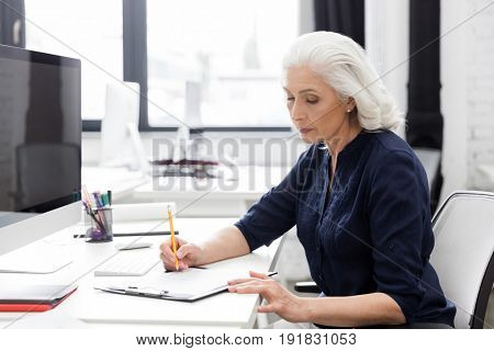 Mature business woman making notes on a piece of paper at her desk
