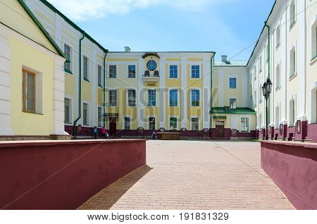 POLOTSK BELARUS - MAY 19 2017: Polotsk State University (complex of buildings of former Jesuit collegium) on Streletskaya Street. Unknown woman with children walks in courtyard near ancient well