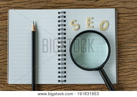 Search engine optimization concept with wooden alphabet abbreviation SEO and magnification glass on note book paper and pencil.
