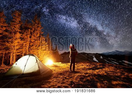 Male Tourist Have A Rest In His Camp Near The Forest At Night. Man Standing Near Campfire And Tent,