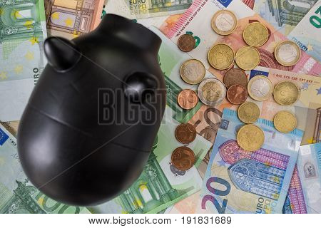 Selective focus on Euro coins on Euro banknotes with black piggy bank as financial saving concept.
