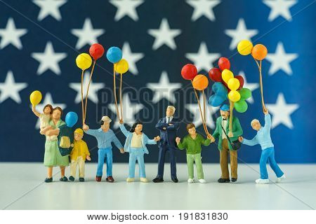 miniature people happy american family holding balloon with United State national stars flag in the background as celebrating the Independence day.