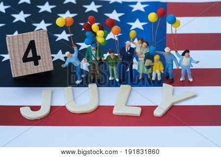 miniature people happy american family holding balloon and wooden block and alphabet as 4 July with United State national flag in the background as celebrating the Independence day.