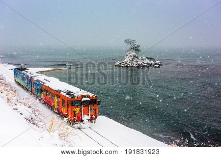 Amaharashi Coast Quasi-national Park, Japan - JANUARY 23, 2017: A Himi Line Train passes the Amaharashi Coast during winter.