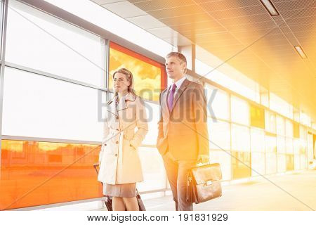 Businesspeople with luggage walking in railroad station