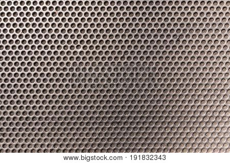 Metallic honeycomb hexagon grilled pattern in front of music speaker as background.