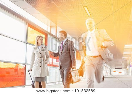 Businesspeople walking while male colleague running in railroad station